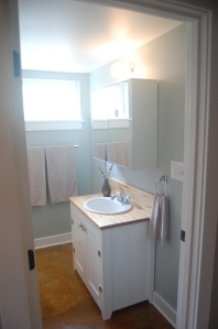 the bathroom sink is salvaged and the vanity made from cabinet-grade plywood scraps