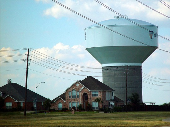 photo of a new tract house with an immense water tower in background